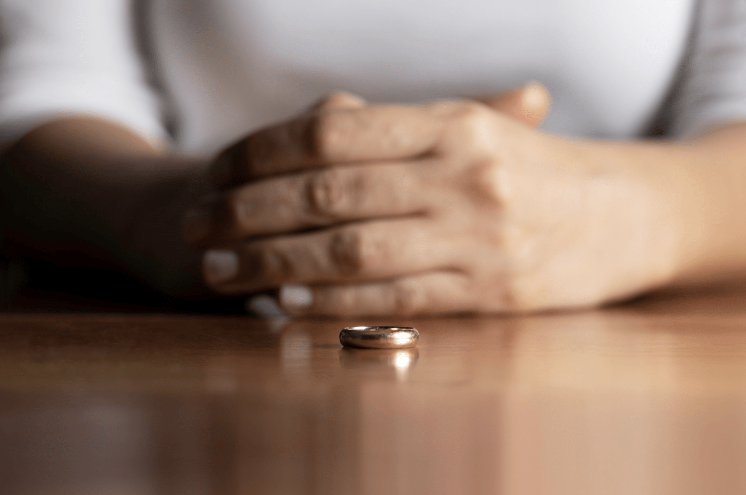 Someone with their wedding ring resting on the table