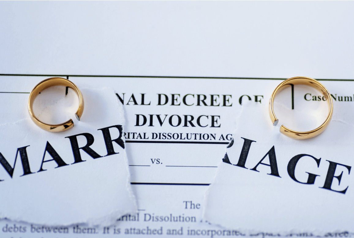 two wedding rings resting on a certificate of divorce